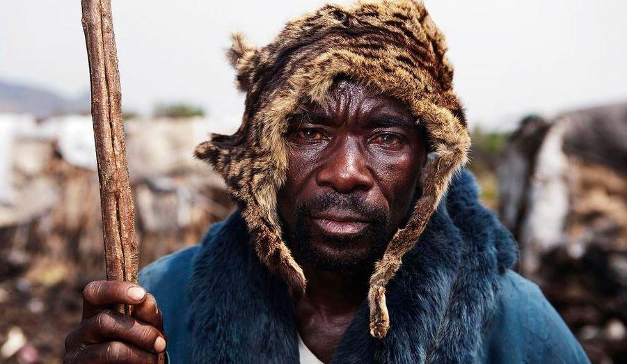 Nzamburba est membre d'une communauté Pygmée en République Démocratique du Congo. Sur sa tête, il porte une peau de chat sauvage.