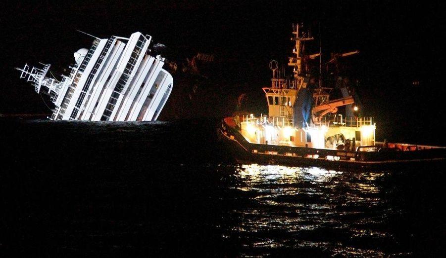 Un navire passe à proximité du Costa Concordia, paquebot de croisière qui s'est échoué vendredi soir sur le récif de Punta Gabbianara, au large de l'île toscane du Giglio.