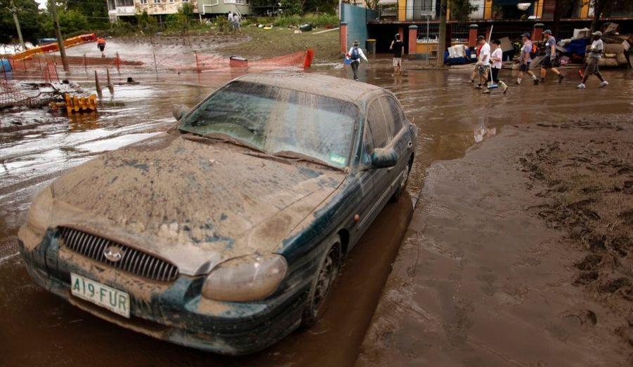 Une voiture recouverte de boue, dans la banlieue de Westend, à Brisbane. Le gouvernement australien a lancé mardi un vaste plan de relance de 20 milliards d'euros pour soutenir l'économie et reconstruire l'Etat du Queensland, dévasté par les inondations depuis le mois dernier.