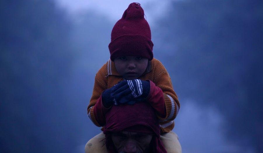 Un petit garçon porté dans son père à Noida, dans la banlieue de New Delhi. Les températures ont chuté dans la région, rapportent les médias locaux.