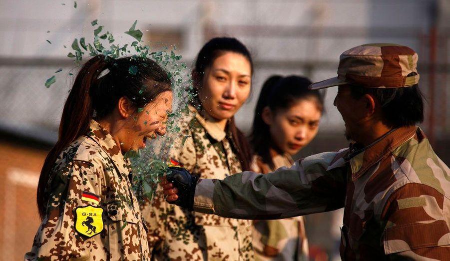 L'entraînement de ces aspirantes gardes du corps se fait sans concession, à Pékin, en Chine. Ici, un instructeur brise une bouteille sur la tête d'une recrue. Ces femmes, qui suivent l'entraînement d'une entreprise privée, sont destinées à devenir, après une formation de 8 à 10 mois, les premières de la profession en Chine.