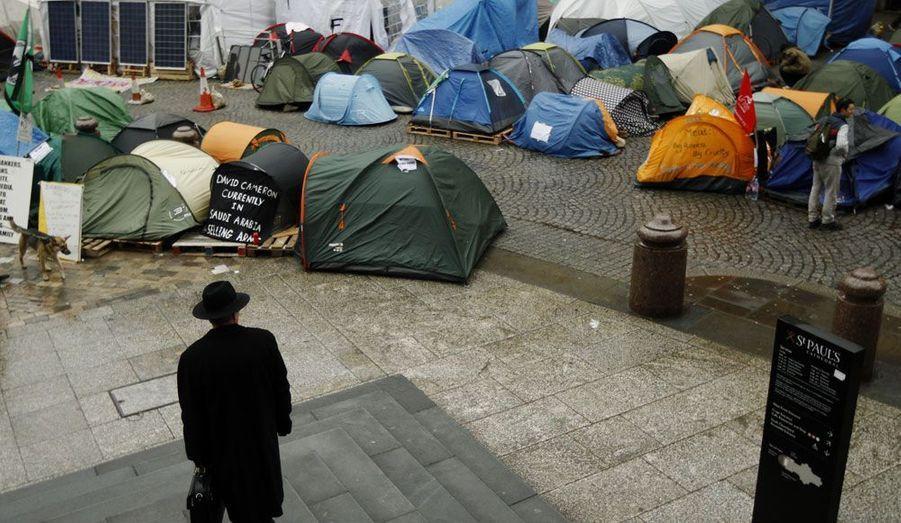 Un homme d'affaire observe des protestataires installés depuis le mois d'octobre à l'extérieur de la Cathédrale Saint Paul de Londres.Les manifestants dénoncent les trop fortes inégalités économiques du pays.