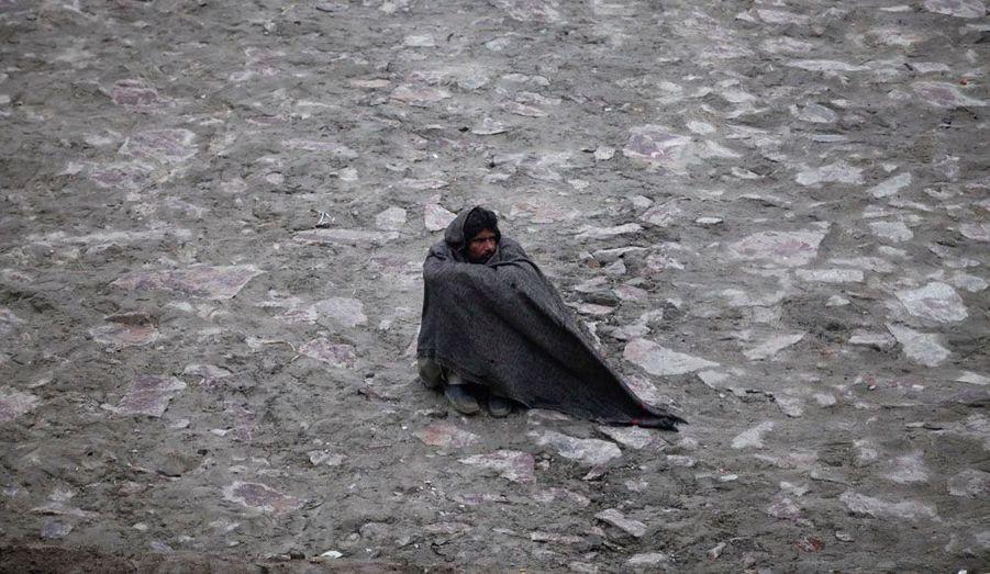 Assis au milieu d'une route du Lahore, deuxième ville du pakistan, cet homme essaye de se tenir au chaud en serrant une couverture tout autour de lui...