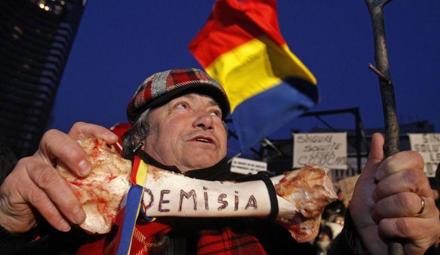 Un protestataire tient un os sur lequel on peut lire le mot «démission» lors d'une manifestation à Bucarest. Les opposants au gouvernement Roumain demandent la démission du Premier ministre Emil Boc.