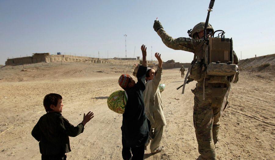 Un soldat américain offre des stylos à de petits enfants afghans, dans le district de Kandahar.
