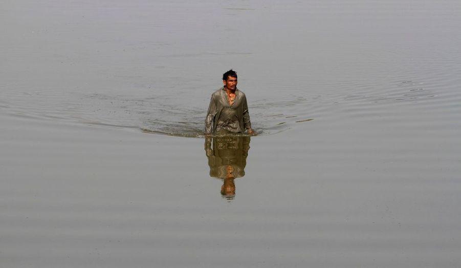 Un homme, déplacé par les inondations, erre dans les eaux de crue qui ont envahi son village de Siddique Solangi, à une vingtaine de kilomètres de Thatta, dans la province de Sindh, au Pakistan.