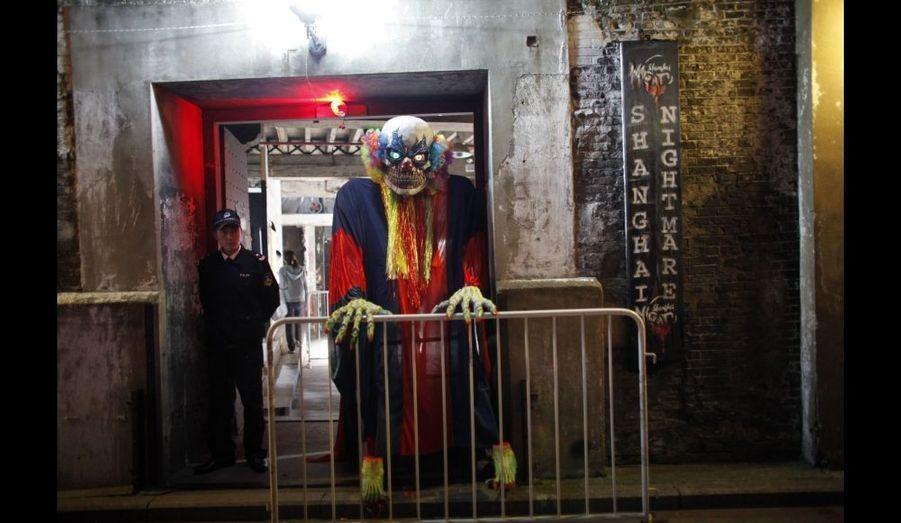 """Un comédien en costume prend une pause devant la maison hantée """"Le cauchemar de Shanghai"""", en Chine, une attraction créée à l'occasion de la fête d'Halloween en 2009. Bien que la Chine ait une longue et riche tradition de fantômes et de célébration des morts, certains pensent pouvoir implanter la fête d'Halloween dans l'Empire du Milieu, même si elle reste inconnue pour la plupart des habitants. Les Chinois célèbrent notamment leur mort lors de la fête Qingmin, généralement en avril."""