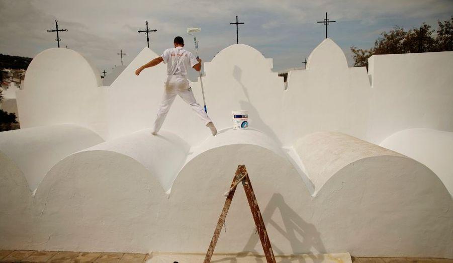 Un homme repeint une pierre tombale du cimetière de Casabermeja, près de la ville espagnole de Malaga, avant la fête catholique de la Toussaint, le 1er novembre.