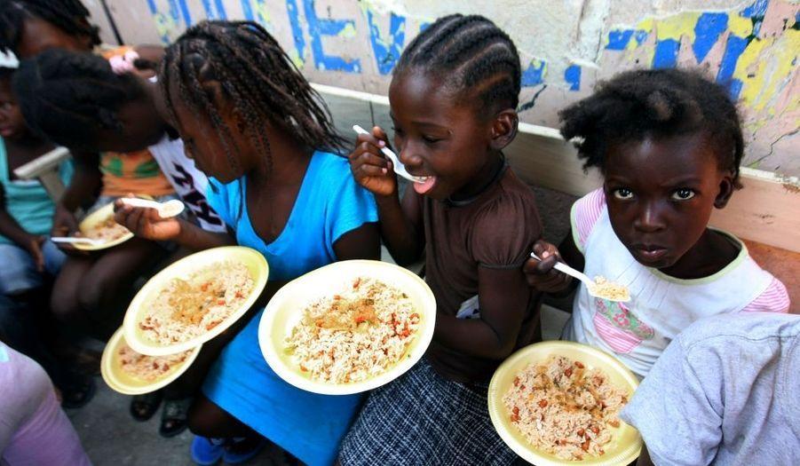 """Des enfants haïtiens sont nourris par l'association OJADH, qui a mis en place une cantine d'urgence après le terrible séisme qui a dévasté l'île le 12 janvier dernier. Grâce à un système de carte jaune, ils """"pointent"""" : ils ont droit à un repas par jour."""