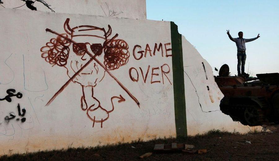 Alors que, comme tous bons dictateurs, Kadhafi a toujours scrupuleusement contrôlé son image public, des portraits caricaturés font leurs apparitions sur les murs en Libye, à la faveur du soulèvement populaire. Ici, à Bengahzi, fief des insurgés qui tentent de faire chuter le dirigeant libyen, au pouvoir depuis 42 ans.