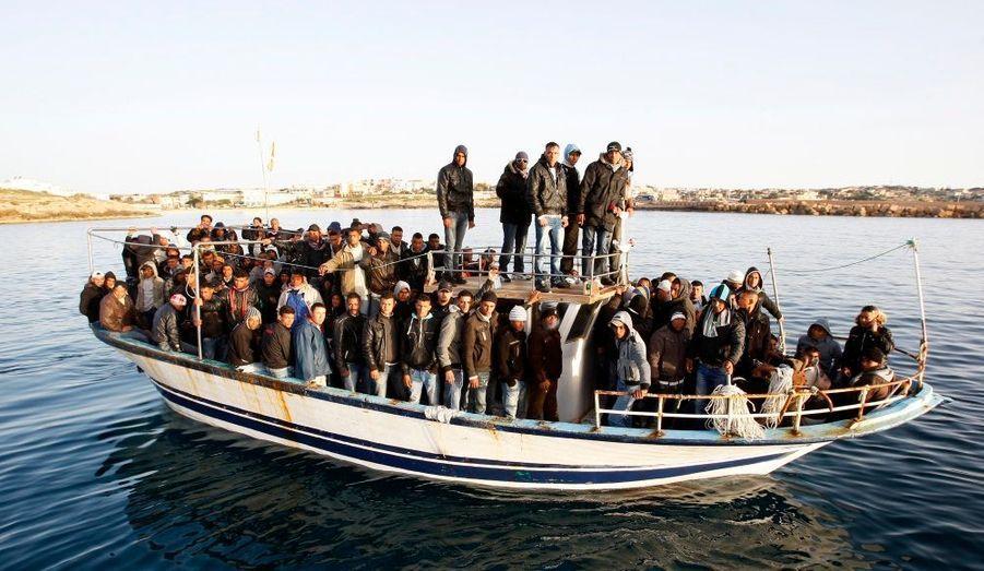 Un bateau de migrants originaires du Maghreb arrive près des côtes de l'île italienne de Lampedusa, fuyant les régimes en place et les révolutions en cours.