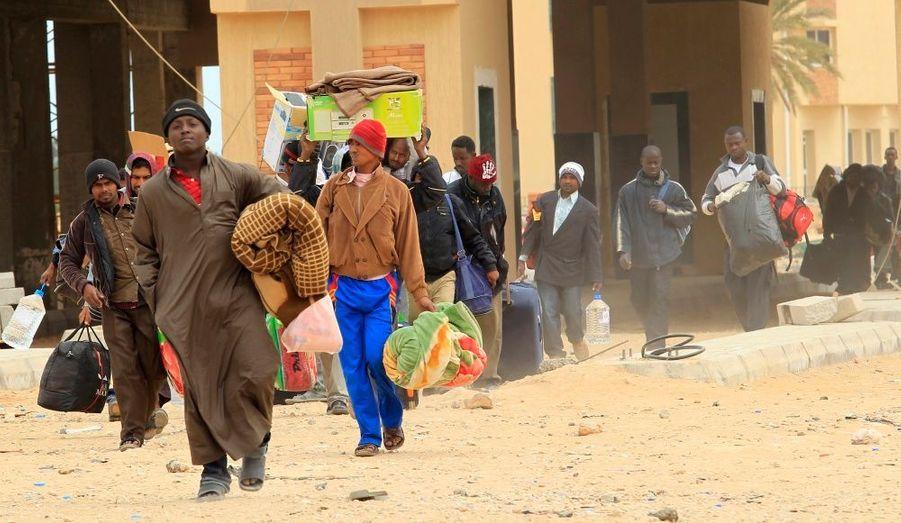 Des travailleurs étrangers fuient la Libye en regagnant la frontière tunisienne à Ras Jedir. Le camp de transit érigé par l'armée tunisienne accueillerait plus de 15 000 personnes.