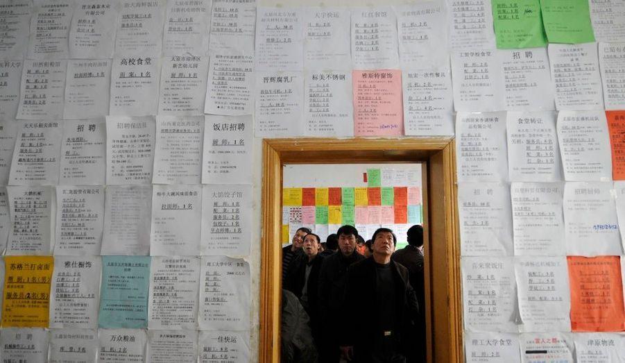 Du pain sur la planche. En Chine, des employés migrants cherchent des informations sur leur futurs emplois.
