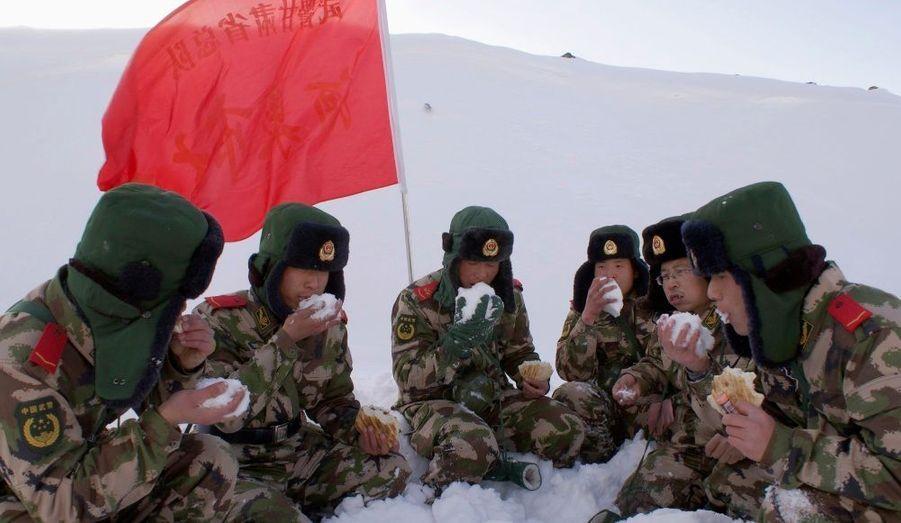 Après une tempête marquée par la mort de beaucoup de bétail, des paramilitaires chinois prennent leur petit déjeuner avec de la neige.