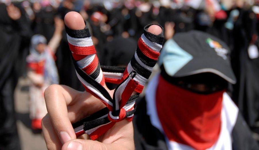 """Une femme fait le """"V"""" de la victoire, les doigts enveloppés d'un ruban aux couleurs du Yémen, lors d'une manifestation à Sanaa pour protester contre une possible immunité du président Saleh, dont le peuple réclame la démission. Un émissaire des Nations Unies s'est rendu dans le pays, jeudi, pour convaincre le dirigeant de quitter le pays sous couvert d'un plan négocié par les pays du Golfe. Le Yémen est en proie à la contestation depuis plusieurs mois. De nouvelles violences ont éclaté dans la ville de Taïz, où les forces de l'ordre ont tiré sur les manifestants."""