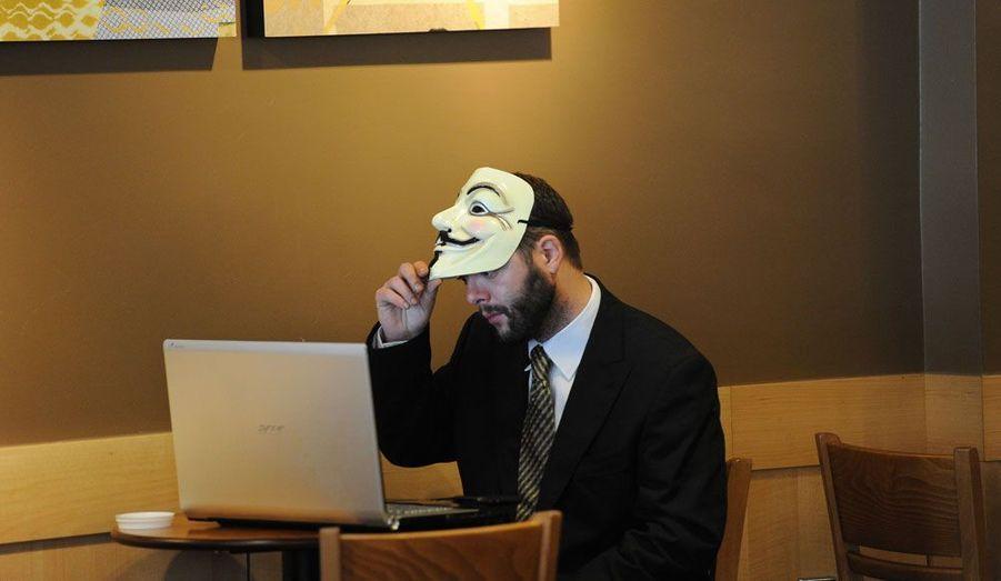 Un «indigné» qui campe devant la cathédrale Saint Paul de Londres consulte son ordinateur dans un cybercafé. Il porte un masque de Guy Fawkes, symbole de résistance adopté par le groupe d'activistes Anonymous.