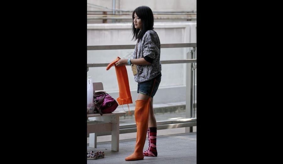 Une femme retire ses bottes en caoutchouc après avoir marché au milieu des rues inondées à Bangkok.