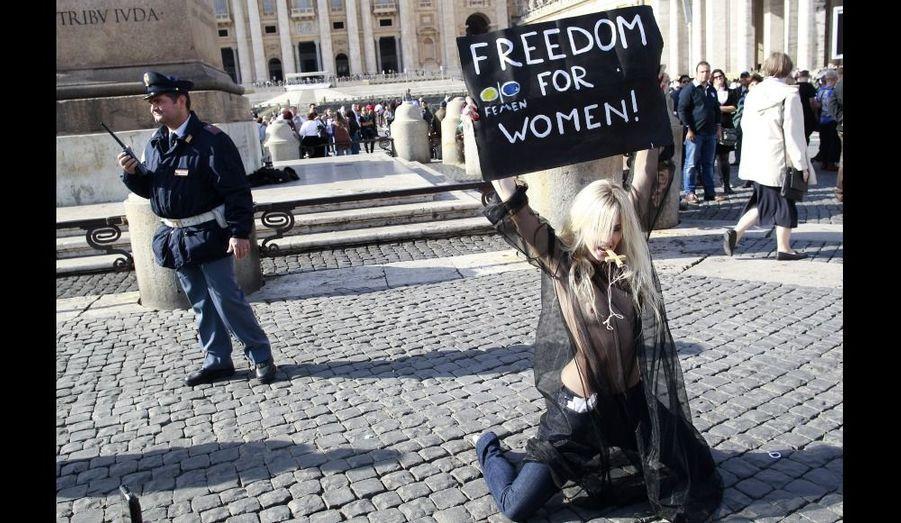 Dimanche à Rome, sur la place Saint-Pierre au Vatican, cette activiste du FEMEN, un groupe de féministes ukrainiennes, brandit une pancarte lors d'une manifestation contre la discrimination à l'encontre des femmes..capitale du pays.