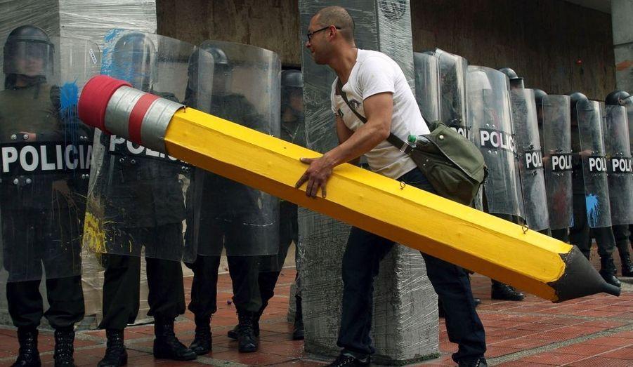 """Un jeune homme tente de """"gommer"""" un barrage de police, lors d'une manifestation à Bogotá, contre la réforme des universités publiques, qui a déclenché un grand mouvement étudiant dans toute la Colombie."""