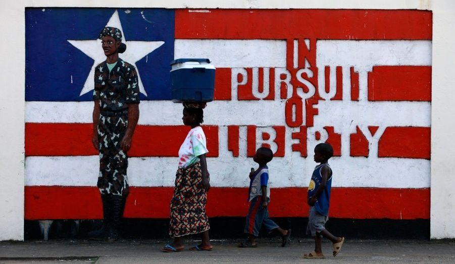 Une femme et deux enfants passent devant une fresque murale en faveur de la liberté à Monrovia, au Libéria.