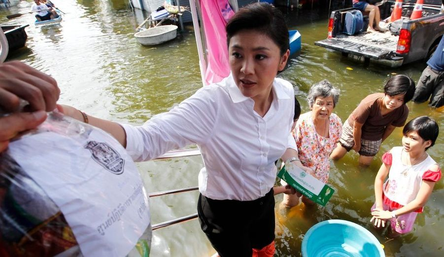 Premier ministre de la Thaïlande, Thaksin Yingluck distribue de la nourriture aux habitants dans une zone inondée de Bangkok.