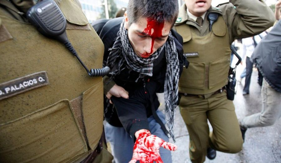 Un étudiant blessé est arrêté par des policiers anti-émeute lors d'une manifestation contre le gouvernement pour une réforme du système éducatif public à Santiago, au Chili.