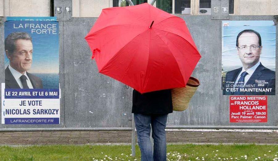 Une passante regarde les affiches de campagne de Nicolas Sarkozy et François Hollande, à Bordeaux, sous la pluie...