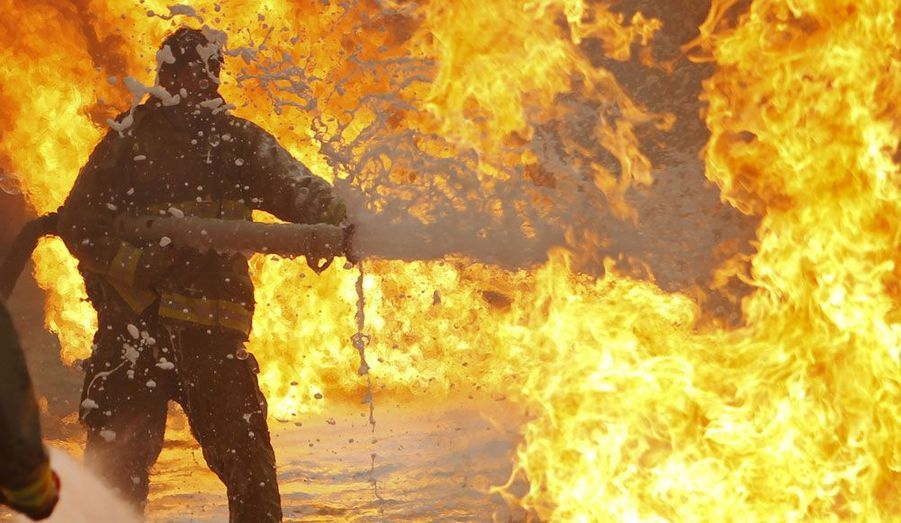 Un pompier pulvérise de l'eau sur un camion-citerne en feu à Kaboul. Les causes de l'incendie sont toujours inconnues. Les autorités ont ouvert une enquête.