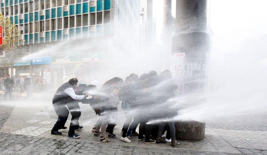 Des étudiants chiliens affrontent le puissant jet d'eau de la police lors d'une nouvelle manifestation à Santiago contre la réforme du gouvernement de l'Éducation nationale.