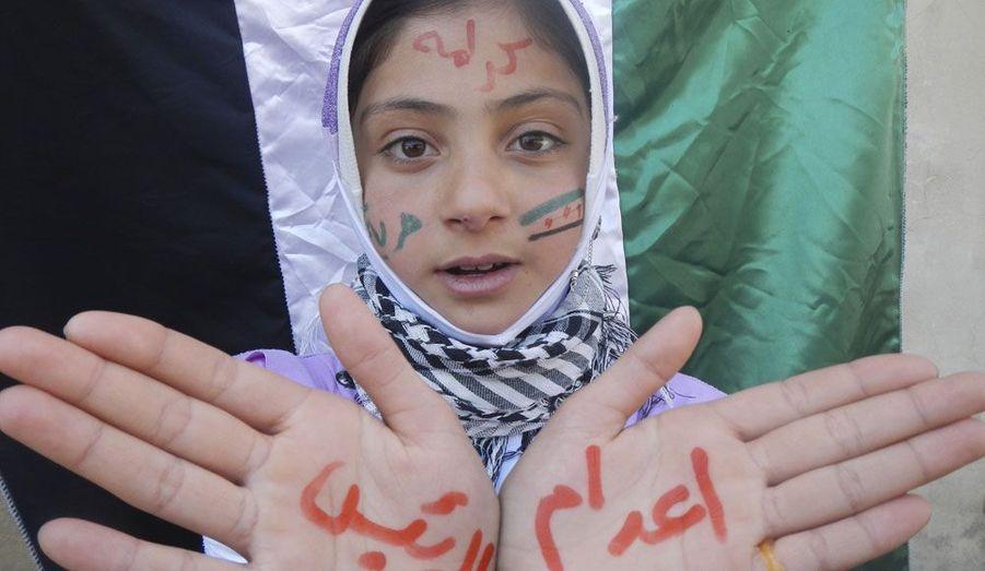 """Une petite fille a pris part à une manifestation contre le président syrien Bachar Al-Assad dans la ville de Kafranbel, près d'Idlib, au nord-ouest du pays. Sur ses mains, on peut le lire le message: """"Exécuter le président""""."""