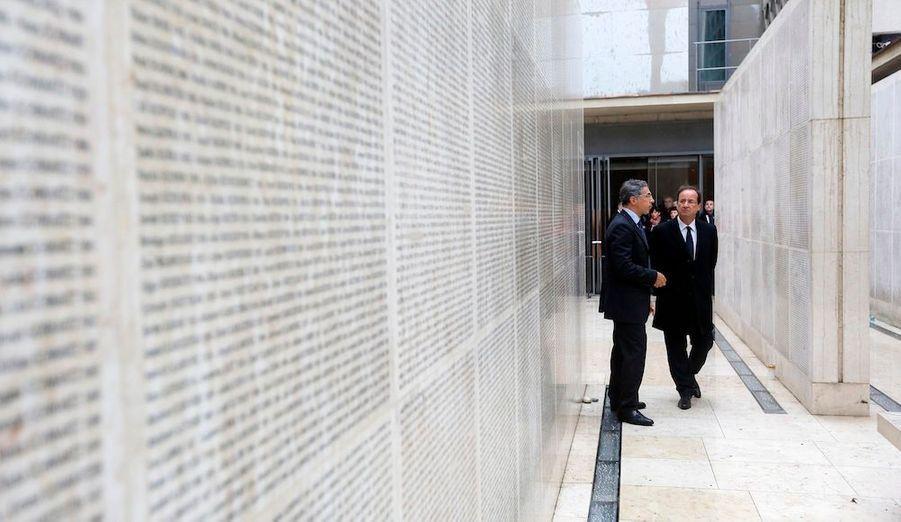 François Hollande écoute le directeur duMémorial dela Shoah,Jacques Fredj, à Paris,à côté dumuroùsont gravés les nomsdes 76 000 Juifsdéportés de France par lesnazis.