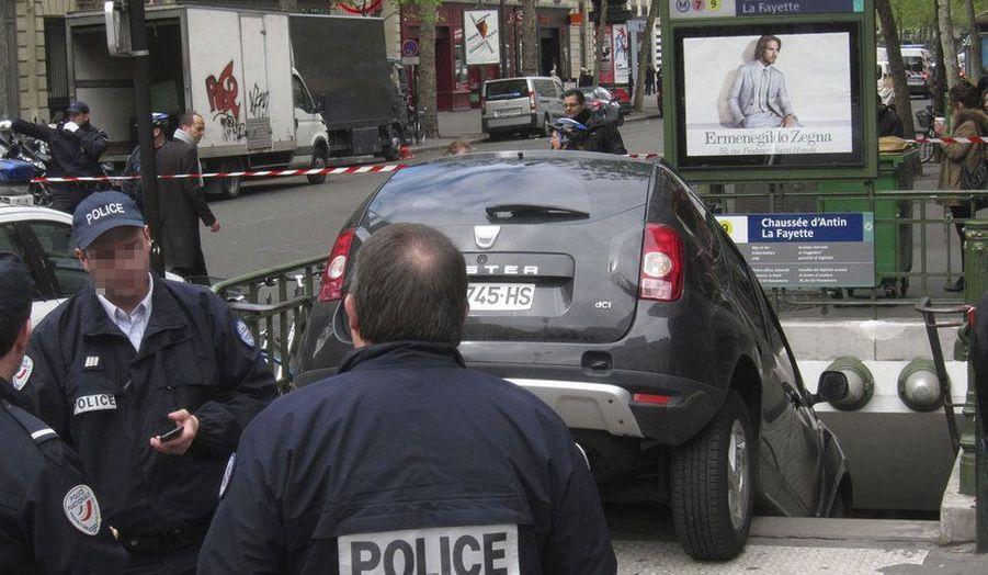 Des policiers parisiens interviennent autour d'une voiture accidentée. Le véhicule a pénétré dans la bouche du métro de la station Chaussé d'Antin – La Fayette dans le 9ème arrondissement sans faire de blessés.