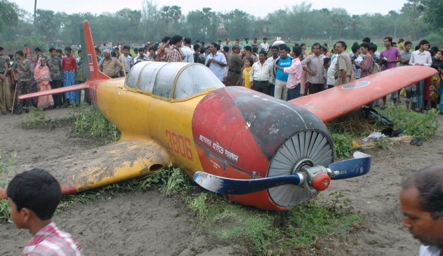 Des badauds tournent autour de la carcasse d'un avion de l'académie de l'Armée de l'air du Bangladesh, après un atterrissage d'urgence près du district de Murshidabad, dans l'est de l'Inde, jeudi. Le pilote est sauf.