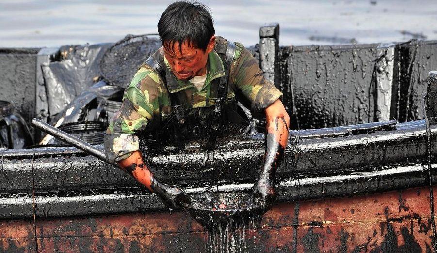 A Dalian, en Chine, un homme tente d'extraire le pétrole qui s'est déversé dans les eaux du port. Le 16 juillet dernier, l'explosion de deux oléoducs utilisés pour le déchargement d'un tanker ont engendré une marée noire.