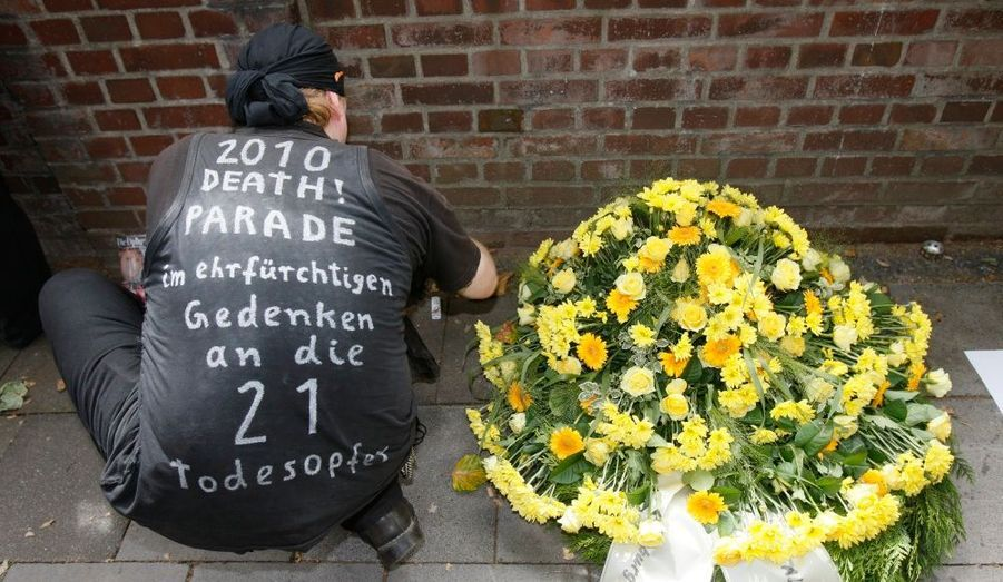 """Un homme dépose des fleurs devant le tunnel où ont péri 21 personnes lors de la """"Love Parade"""", à Duisbourg en Allemagne. Une cérémonie religieuse s'est tenue aujourd'hui à l'église de la ville, où se tenaient de nombreuses personnalités politiques allemandes, notamment la chancelière angela Merkel."""