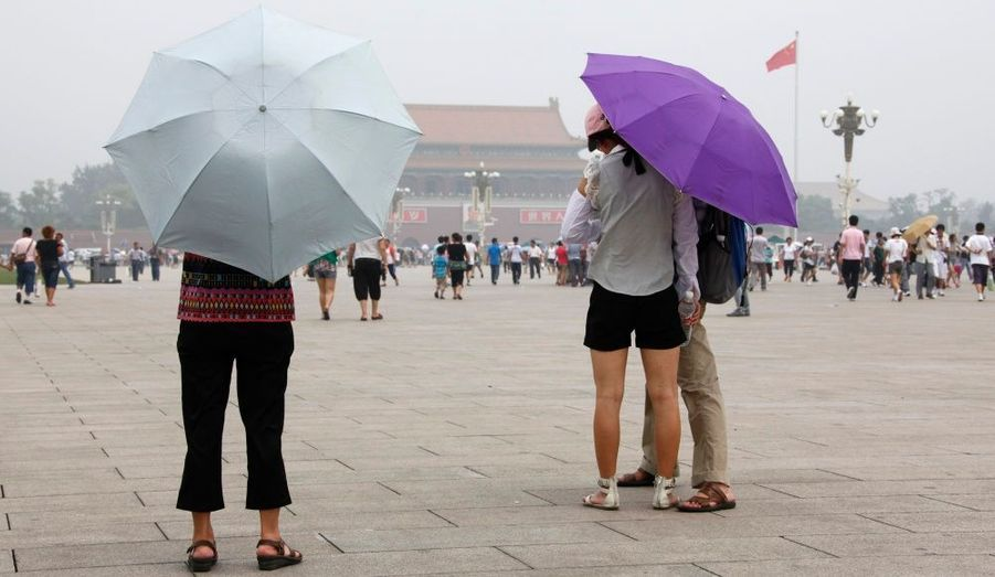 Des touristes visitent la place Tian'anmen, à Pékin, en se protégeant du soleil avec des parapluies.