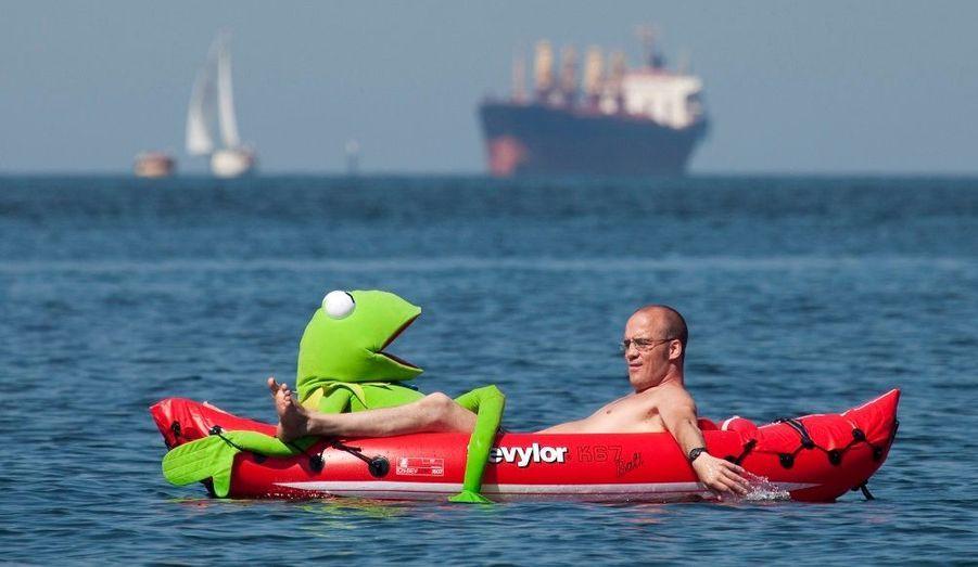 Un homme se rafraîchit dans la Baie des Anglais, à Vancouver, en compagnie d'une peluche Kermit la grenouille.
