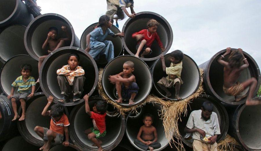 Des enfants jouent dans les conduites d'eau d'un chantier au bord de la rivière Yamuna, à Allahabad, en Inde.