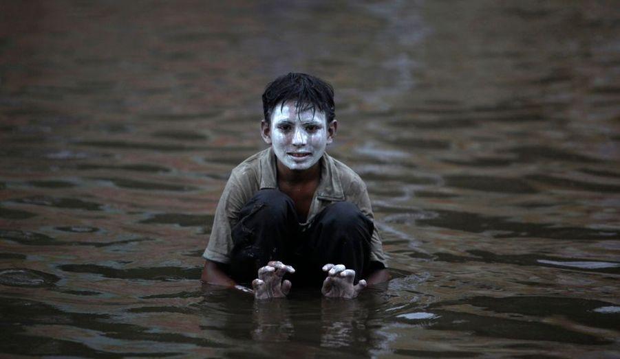 Un enfant grimé est assis dans les eaux de la mousson à Karachi. Des pluies diluviennes frappent actuellement le Pakistan. Ces intempéries pourraient être la cause du crash d'un Airbus près d'Islamabad ce mercredi.