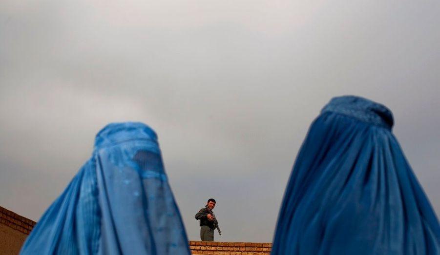 Deux femmes attendent la distribution de l'aide d'hiver aux réfugiés à Kaboul, par les Nations Unies, sous la surveillance d'un policier.
