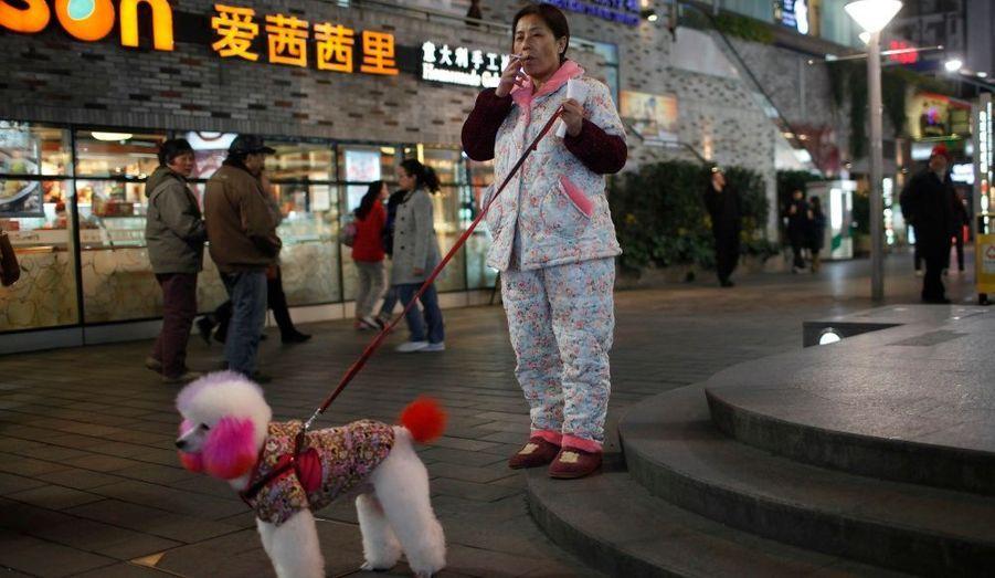 Une femme fume une cigarette, en sortant son caniche teint sur les trottoirs de Shanghai.