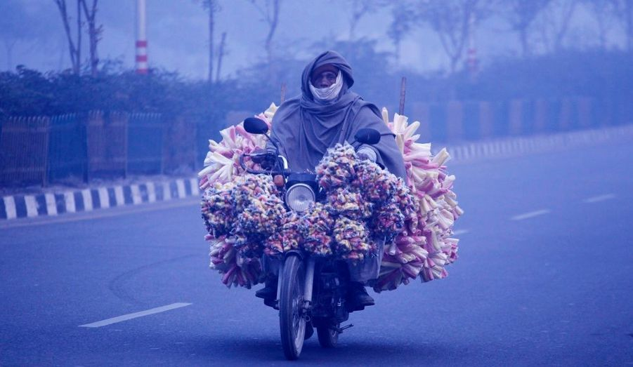 Un homme sur une moto chargée de victuailles traverse dans le matin froid la ville de Noida, près de New Delhi en Inde.