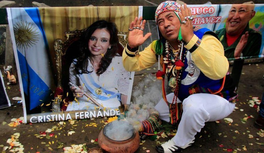 Un chaman péruvien pratique un rituel devant des photos de deux dirigeants de pays voisins, l'Argentine Cristina Fernandez et le Vénézuelien Hugo Chavez, tous deux atteints d'un cancer, lors d'une célébration pour 2012 sur la colline de San Cristobal à Lima.