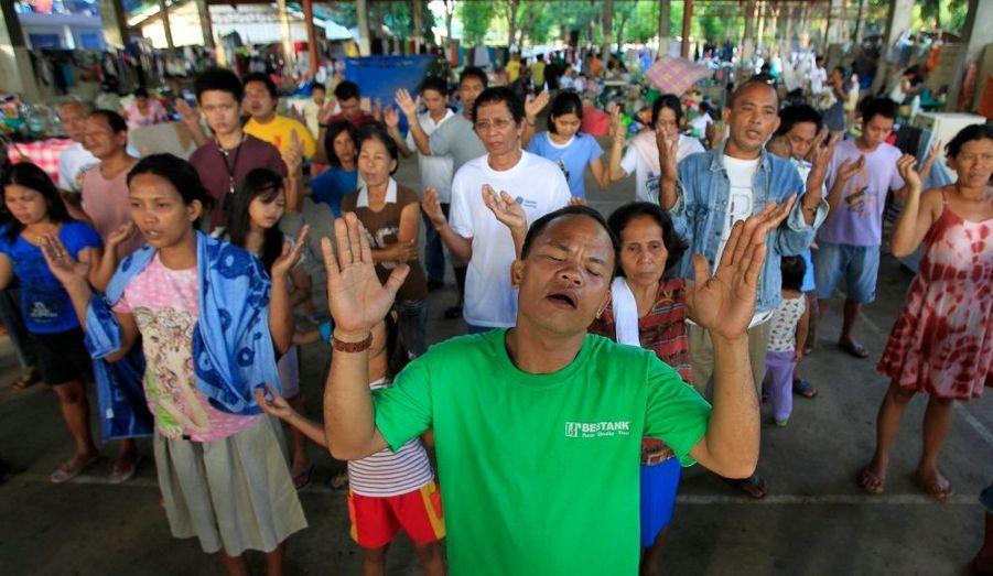 Des survivants du typhon Washi prient lors d'une messe publique, dans une école transformée en camp, à Cagayan de Oro, dans le sud des Philippines. Le typhon ca causé près de 1300 morts, et 1100 personnes sont toujours portées disparues.