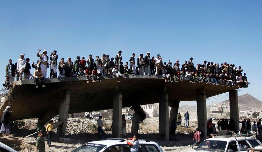 A Taiz, des gens, installés sur le toit d'une maison détruite, observent les manifestants anti-gouvernementaux lors de leur marche vers la capitale yéménite Sanaa.