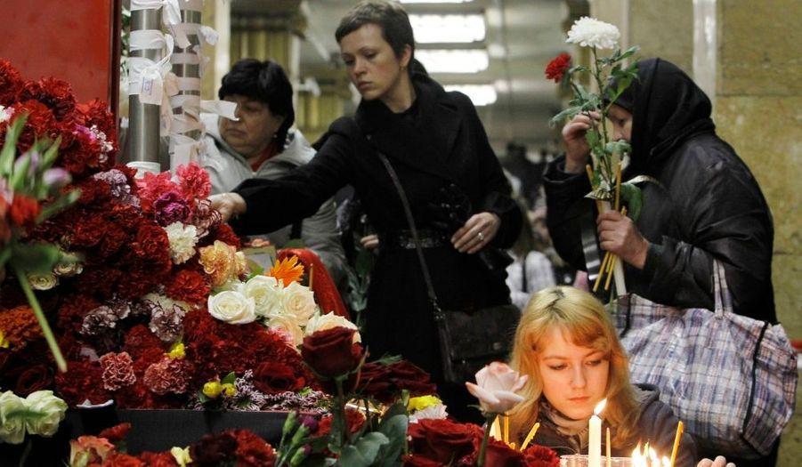 Des Moscovites déposent des fleurs et allument des bougies à la station de métro Park Kultury, en mémoire aux victimes des attentats qui ont fait au moins 37 morts hier dans la capitale russe.
