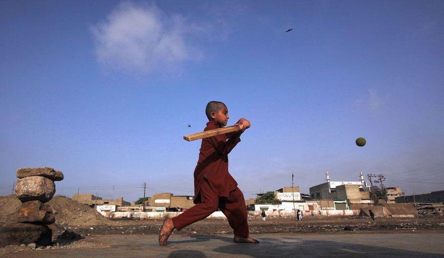 Près de Karachi, au Pakistan, un enfant joue au cricket sur un terrain proche d'un bidonville.
