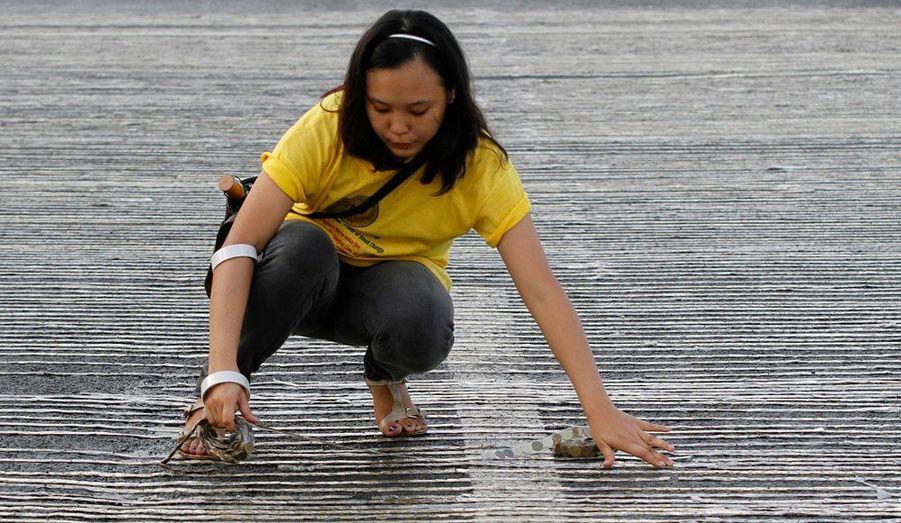 A Manille, aux Philippines, une bénévole comble les vides dans une ligne de pièces de monnaie réalisée avec pour objectif de battre le record du monde de longueur de pièces de monnaie. Jusqu'à présent, le prestigieux titre est détenu par les Etats-Unis, avec 64,8 km. L'équipe philippine a réuni 3,5 millions de pièces pour atteindre les 70 km.