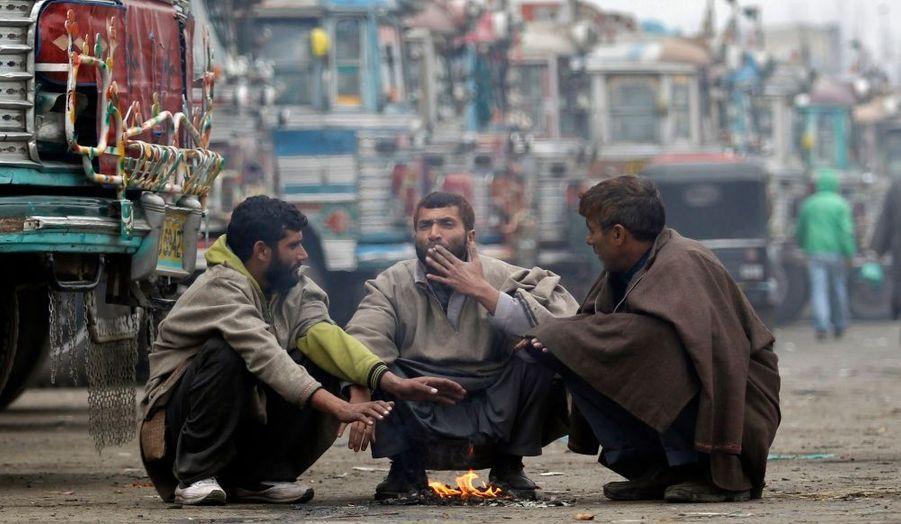 Des hommes se réchauffent à proximité d'un dépôt de bus à Srinagar, ville du nord ouest de l'Inde.