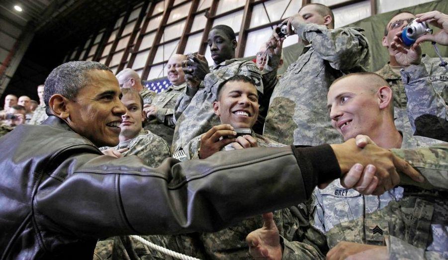 """Le président Barack Obama a effectué vendredi une visite surprise en Afghanistan où il est toutefois resté sur une base militaire américaine, le mauvais temps l'ayant obligé à annuler un déplacement à Kaboul où il avait prévu de rencontrer son homologue afghan Hamid Karzaï. S'adressant à près de 4.000 soldats sur la base aérienne de Bagram, non loin de la capitale, le chef de la Maison blanche a déclaré que des """"progrès très importants"""" étaient accomplis contre les insurgés depuis l'envoi de renforts américains."""